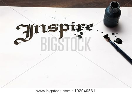 Inspire calligraphy . Artist workplace. Ink word on sheet of paper and pen top view. Drawing lessons, art school, creativity bacground concept