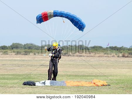 Landed Skydiver Looks As Though He Has Extra Small Chute (other Diver Landing Behind Him)