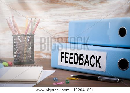 Feedback, Office Binder on Wooden Desk. On the table colored pencils, pen, notebook paper.