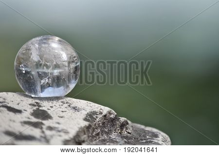 Quartz crystal ball on rock with pastel background