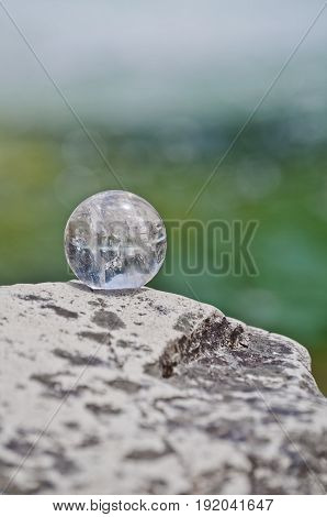 Quartz crystal ball on rock with blue green soft focused background
