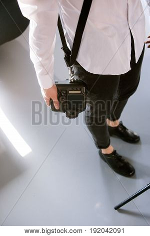 Unrecognizable photographer with camera. Man in studio holding professional photocamera.