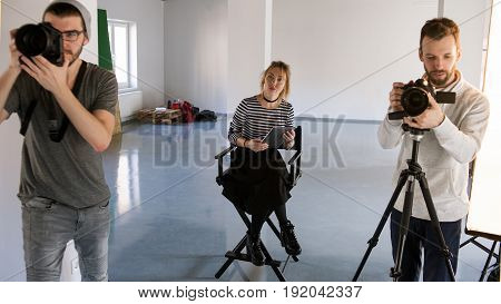 Big creative team working in studio. Photographer and videographer working while art director observing. Production of commercials backstage