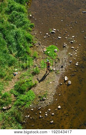 The fisherman in swimming trunks and kepi is fishing on the river bank.View from above