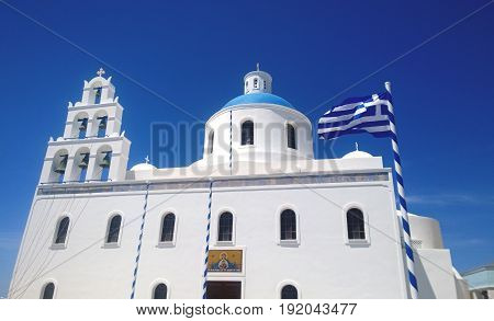 Orthodox Church Panagia in the village of Oia in Santorini with developing the flag of Greece