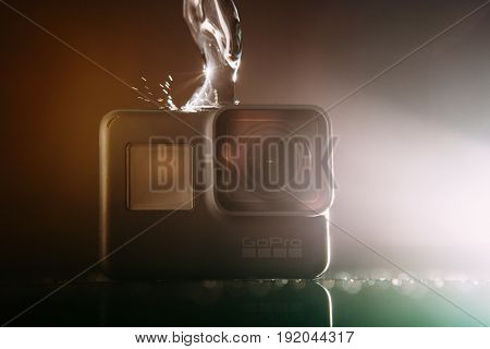 Kharkov, Ukraine - April 13, 2017: GoPro HERO 5 digital action camera with water with lensflare on black. Compact gadget waterproof , support 4k video and is often used in extreme photography
