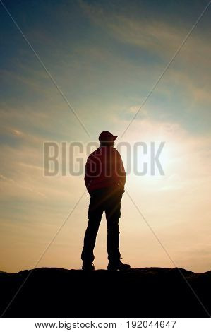 Silhouette Human Standing On Rocky Pedestal On Nature Daybreak  Background.