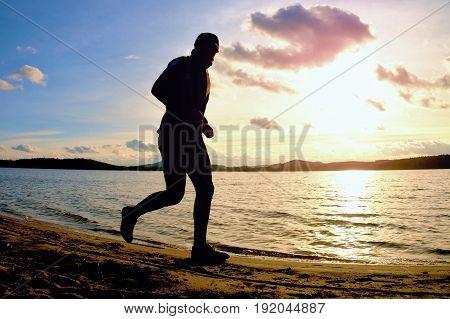 Tall Man With Sunglass And Dark Cap Is  Running On Beach At Autumn Sunset