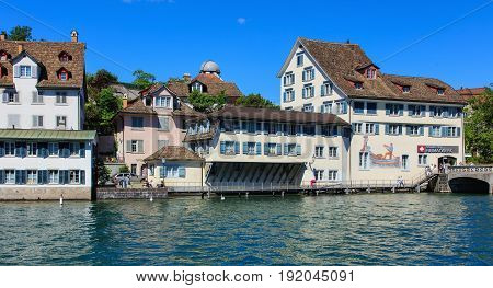 Zurich, Switzerland - 18 June, 2017: historical buildings along the Limmat river, people on the embankment of the river. Zurich is the largest city in Switzerland and the capital of the Swiss canton of Zurich.