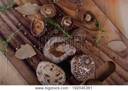 top view dried shiitake mushroom with herb on wooden board