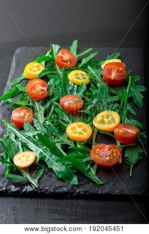 Arugula Salad With Kumquat And Tomato Cherry On Slate Plate. Healthy Food. Diet.