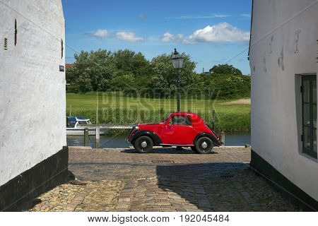 RIBE DENMARK - JUNE 174 2017: Red vintage car and cobblestone street from royal town Ribe in Denmark