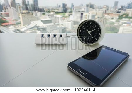smartphone with USB hub and modern minimal clock on office desk