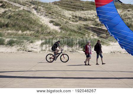 FANOE DENMARK JUNE 17 2017: Cyclist and spectators are looking at a big circle kite on Fanoe beach. Fanoe Kite Fliers Meeting June 2017.