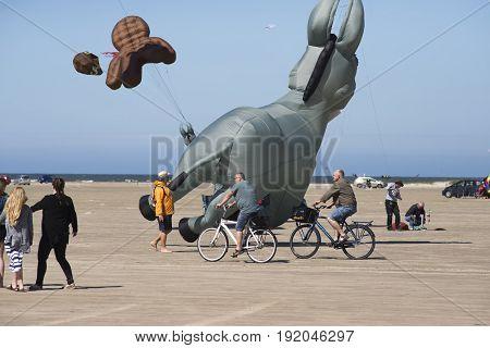 FANOE DENMARK JUNE 17 2017 Cyclists and spectators past a donkey kite on Fanoe beach. Fanoe Kite Fliers Meeting June 2017.