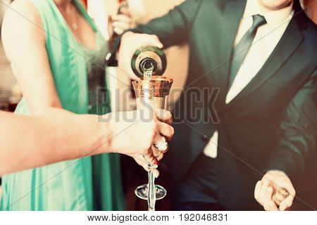 Man in suit pours champagne into a glass. Champagne party