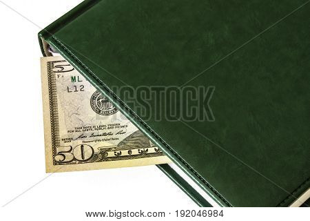Between the sheets of the closed diary is visible part of the bill of 50 dollars
