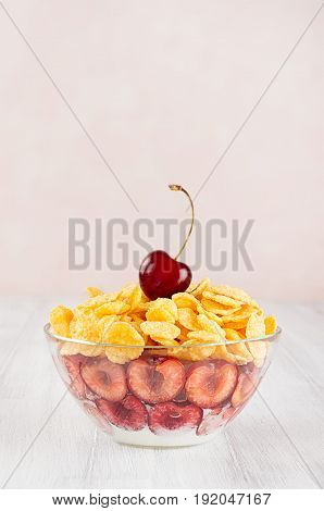 Delicate pink breakfast with golden corn flakes decorated cherry on white wood board.