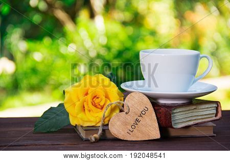 A cup of summer tea on a stack of books and a fragrant yellow rose. Romantic concept. Copy space