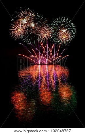 Firework. Beautiful Colorful Fireworks On The Water Surface With A Clean Black Background. Fun Festi
