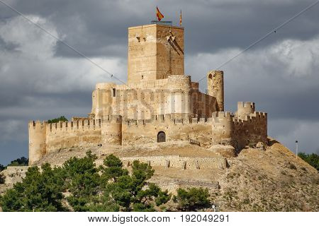 Top of the hill with Biar castle in Alicante with dark clouds, Spain