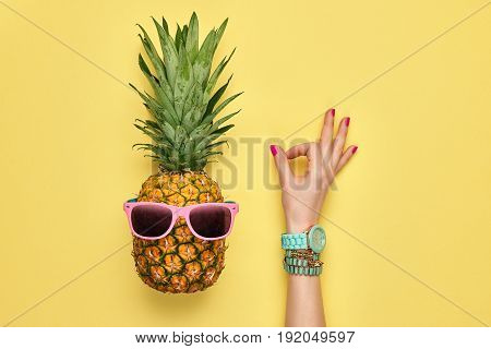 Fashion Hipster Pineapple. Female hand OK, Gesture Stylish Trendy Watches, Glamor Accessories. Bright Summer Color. Tropical pineapple, Sunglasses. Creative Art concept. Minimal. Summer background