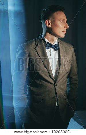 Stylish bridegroom in gray suit and butterfly posing in hotel