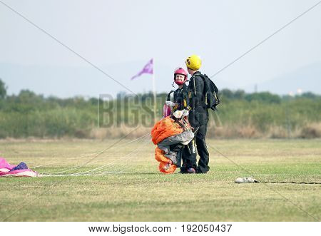 Man And Woman Skydiving And Lover Partners Talking After Successful Landing
