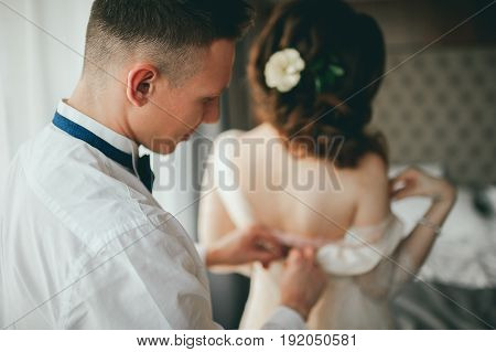 The groom dresses the bride. Wedding preparations