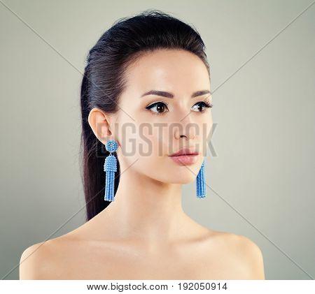 Cute Girl with Earrings. Fashion Portrait of Beautiful Woman