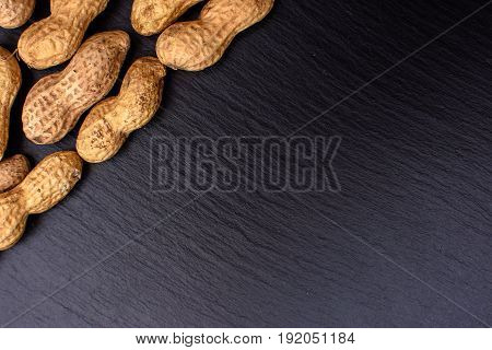 Unclean Peanuts Lie On A Black Stone Board In The Form Of A Frame, Space For Text