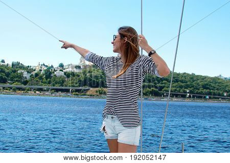 woman in the boat on the Dnieper River in sunglasses. Pretty sail woman looking sideways and smile