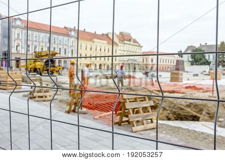 View on the construction site through a fence wire with quadratic shape.