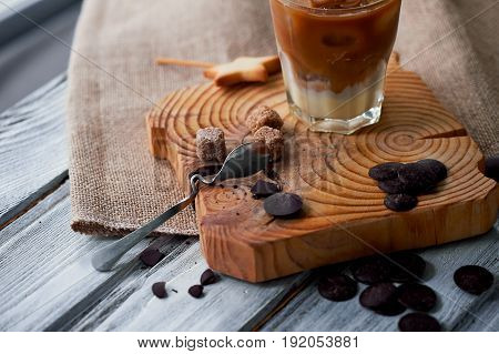 The Hong Kong iced coffee in a glass, with a straw. interesting wooden background