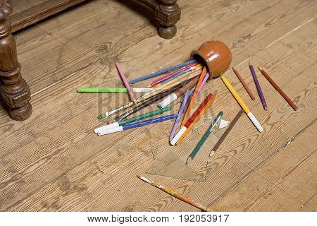 Pencils, broken glass and painting brushes dropped on the wooden floor. Focus in the foreground