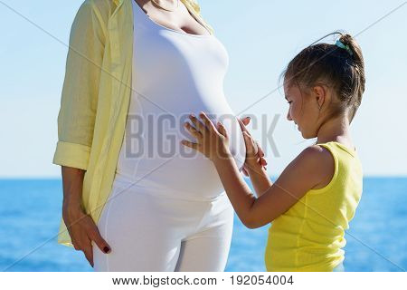 Young European Daughter Is Touching Tummy Of Her Pregnant Attractive Mom Close To The Sea Under Blue