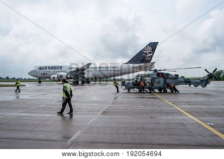 BERLIN GERMANY - JUNE 01 2016: A helicopter AgustaWestland AW159 Wildcat. Black Cats (Royal Navy Display Team) in the foreground and Iron Maiden's Boeing 747