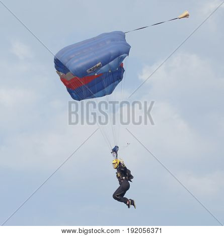 Female Sky Diver With Brightly Coloured Open Parachute Landing At Speed