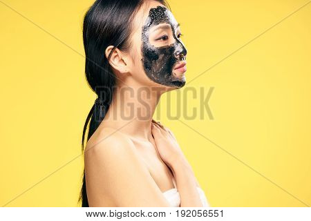 Woman in a cosmetic mask, facial, woman on a yellow background.