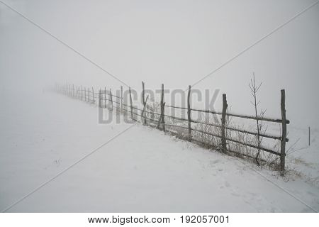 Wooden fence in the field with snow and fog