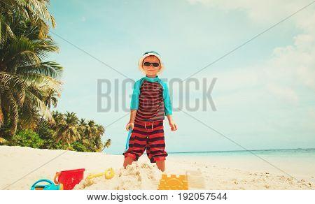 little boy play with sand on tropical beach