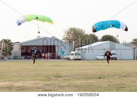 Two Skydivers Landing Simultaneously With Open Parachute.