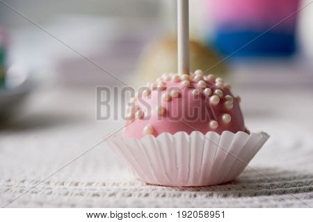 cake pop on a stick on a wooden background. Beautiful candy pastel shades