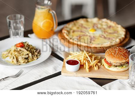 beautiful table of italian pasta, pizza, burger and drinks. hearty lunch in the afternoon. focus on the burger.