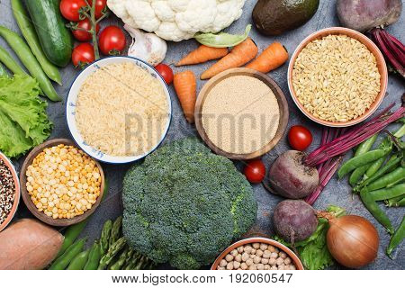 Variety ofrains in bowls and vegetables, broccoli, squash, beans, tomatoes, carrots, avocado, quinoa, peas, rice, oats, selective focus