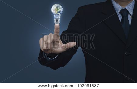 Businessman pressing earth globe in light bulb over blue background Energy conservation and environmental concept Elements of this image furnished by NASA