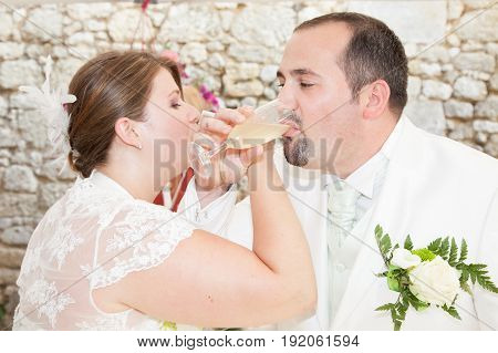 a bride and groom drinking together champagne