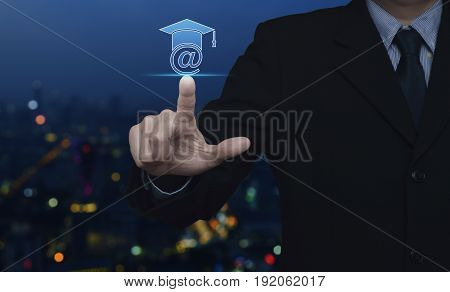 Businessman pressing e-learning icon over blur colorful night light city tower Study online concept