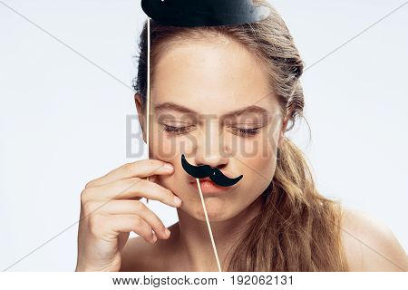 Holiday, woman with a mustache on a stick, a paper mustache, a woman on a light background, a carnival card mask, masks for a photo shoot.