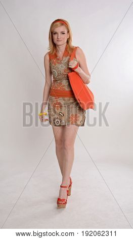 Style of the 1970s. Beautiful long-haired blonde in a short dress on a white background. A model hairstyle, high heels, colorful accessories, a red bag. Retro fashion.